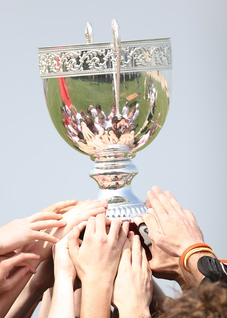 Photograph of a trophy with the team holding it reflected on the cup.
