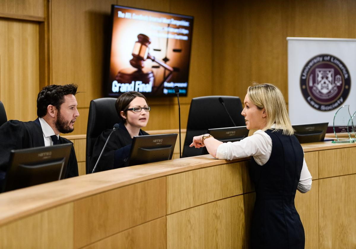 Image of the moot courtroom in use, a man and a woman seated and one woman at the bar