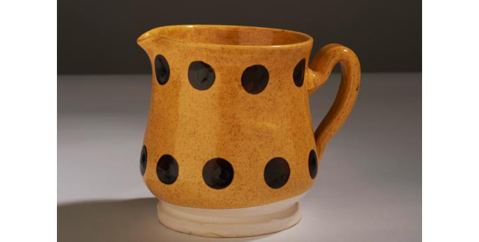 CR108 IACI.2002.255 Williamsburg Pitcher White clay, three quarter covered in a rich mustard yellow glaze, with eighteen raw umber dots patterned in two bands on the exterior. The handle is loosely formed and has two horizontal lines above and between the grip. The interior is undecorated. (Stamped in blue on base, Williamsburg Restoration C 4 W X X) 11.4 x 13.8 x 10.7 cms United States Pottery