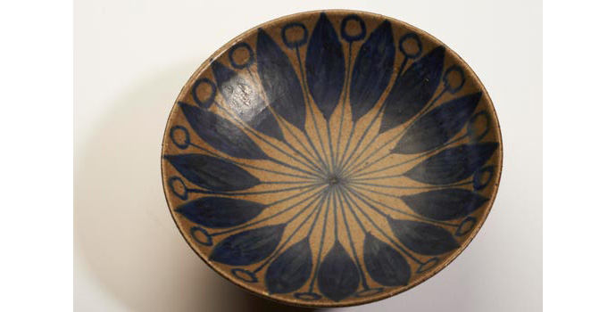 CR78 IACI.2002.233A&B W Footed bowl Dark brown clay, two thirds glazed in a green-grey slip, on the exterior, leaving the foot unglazed. Interior green-grey glazed and patterned with sixteen hand drawn petal shapes in a cobalt blue slip. The stems of which continue and merge in the centre of bowl. Between the leaves are sixteen more stems, which finish in blurred circles around the upper edge. (Stamped on base, Denmark, and inscribed W 41). 6.2 x 16.1 x 16.1 cms Denmark Ceramic