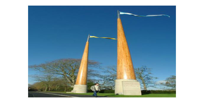 Gate Masts, Shane de Blacam. Laminated solid wood polished and varnished. The base is fitted with steel plates bolted through the curved stone base to piled foundations. 25m high x 1m base to 200mm top - Located on grounds, main entrance to campus.